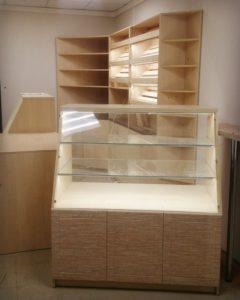 Торгово-выставочная мебель для пекарни. Высота наклонных прилавков: 1,3 м. Цвет: дуб сонома. Под каждой полкой установлена светодиодная подсветка.