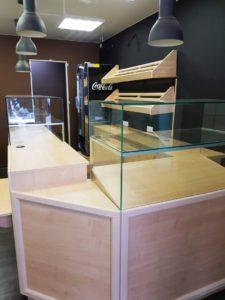 Торговое оборудование для пекарни. Характеристики проекта: 1) три витрины со стеклянным коробом, склеенным на УФ-склейку. Стекло 8мм, подсветка под стеклом теплого оттенка; 2) кассовый прилавок с подсумком; 3) закрытый угловой сегмент 4) пристенный комод с выдвижными ящиками и замками 160 см. 5) тумба под кофемашину 6) хлебные полки из массива дерева (липа) - 160 х 33 х 33  Цвет: клён. Все фасады декорированы багетом белого цвета